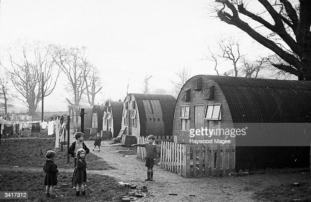 Children beside a row of Nissen huts at Duddingston Camp in Edinburgh The basic tin shelters were built as temporary accommodation for families whose...