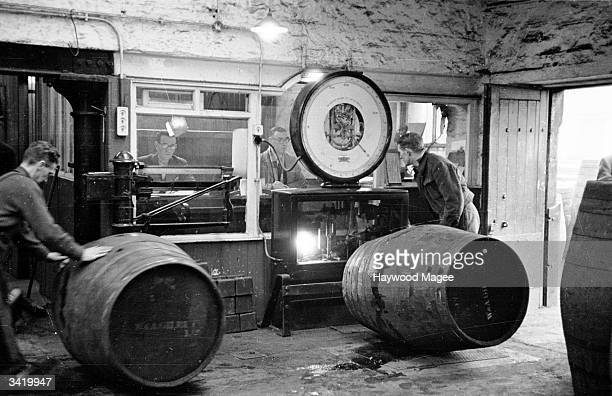 Excise men counting barrels of whisky as they are rolled through the North British Distillery in Edinburgh The distillery produces 67000 gallons a...