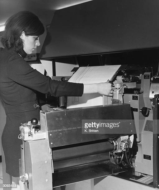 A computer operator sets up continuous stationery on an IBM 1403 model NI line printer The printer is used with an IBM 360 computer and prints at...