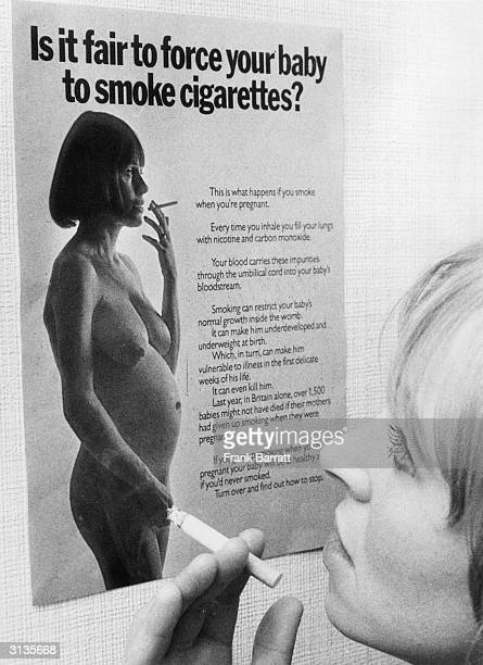 A woman with a cigarette in her hand reads a Health Education Council poster warning her against the dangers of smoking during pregnancy The slogan...
