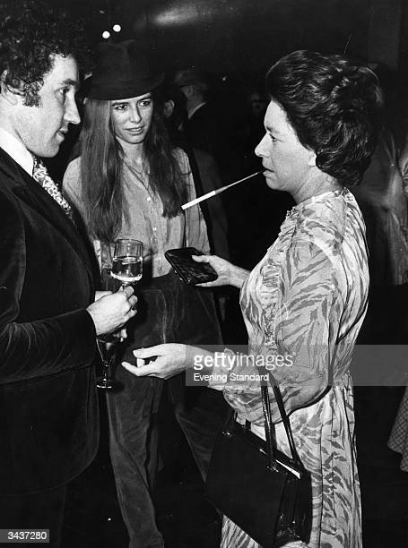 With a long cigarette holder Princess Margaret Rose younger daughter of King George VI and Queen Elizabeth and sister of Queen Elizabeth II talks...