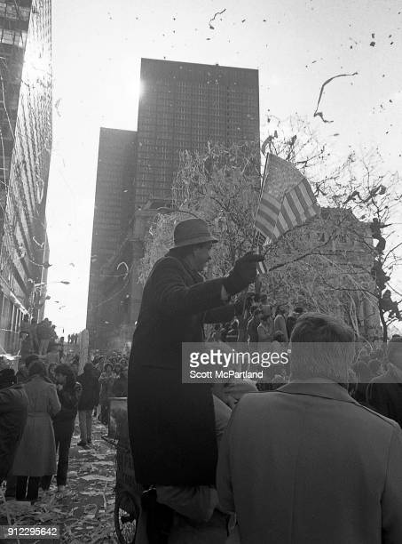 New York A man sitting on his friends shoulders waves American flags during a ticker tape parade The parade is celebrating the release of the...