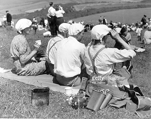 Four racegoers to the fourday Summer Meeting at Goodwood Racecourse who used their handkerchiefs as emergency sun hats to guard against the hot...