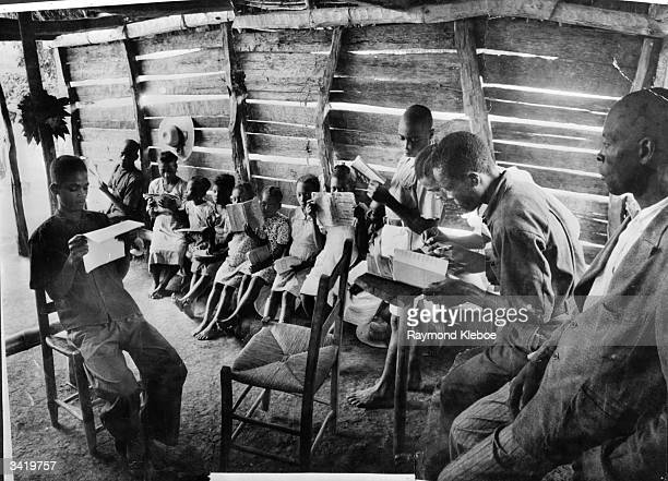 Learning to read Creole, which will be used to teach French, the official language, at a school set up by UNESCO . Original Publication: Picture Post...
