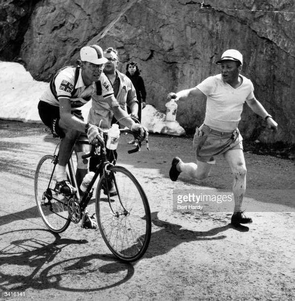 British cyclist Bob Maitland is passed a water bottle as he takes part in one of the hardest stages of the Tour de France between south Briancon and...