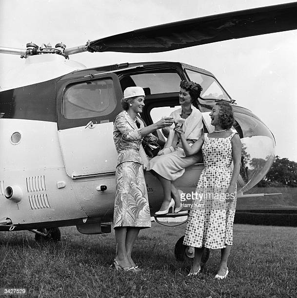 Three ladies at a helicopter garden party hosted by British actress Florence Desmond at Duneborough House Ripley Surrey 400 guests arrived in...