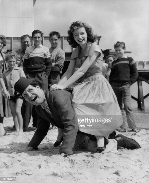 Comic conjuror Tommy Cooper , wearing his trade mark fez, gives a ride to singer Ruby Murray on the sands at Yarmouth, Isle of Wight.