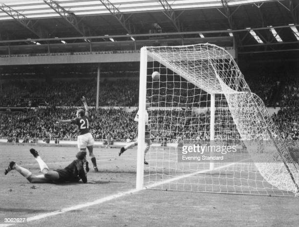 English player Roger Hunt raises his arms in celebration convinced that the ball had crossed the line from a shot by Geoff Hurst that hit the...