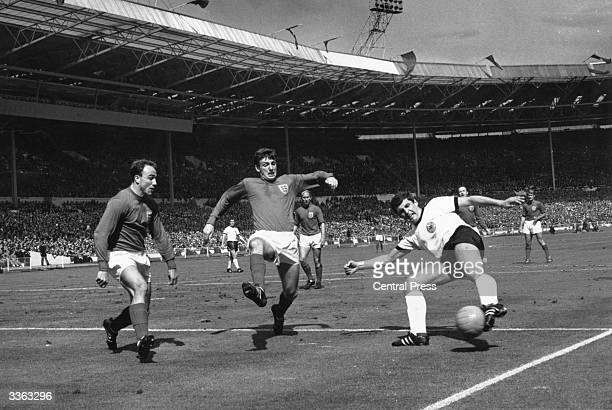 George Cohen and Martin Peters in action for England during the World Cup Final match against West Germany at Wembley Stadium London