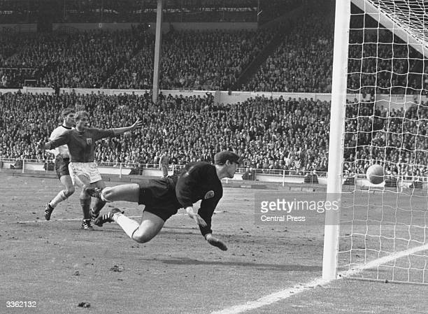 German goalkeeper Hans Tilkowski dives for the ball during the final of the World Cup between England and Germany at Wembley Stadium He is watched by...