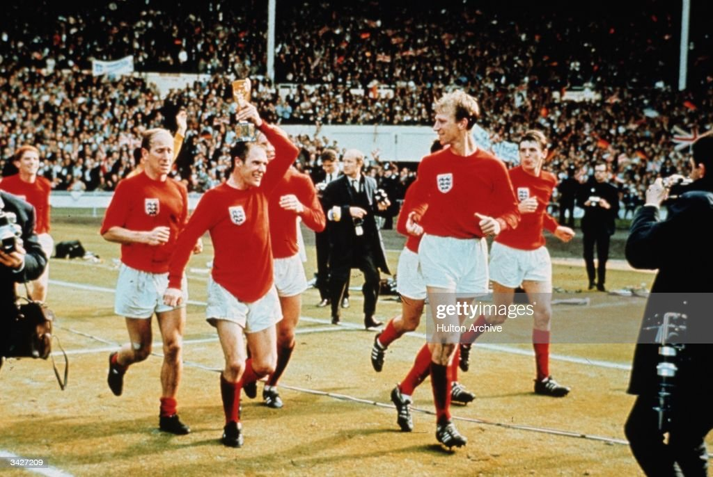 Ray Wilson (holding the trophy) performing a lap of honour with the Charlton brothers at Wembley after England won the World Cup against West Germany 4-2.