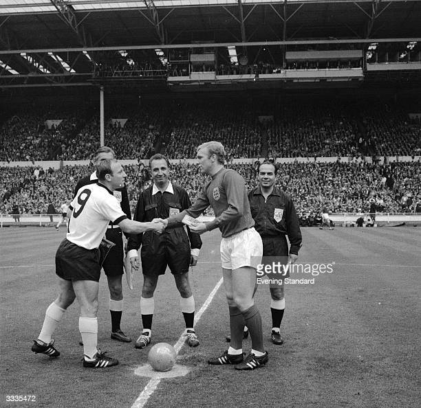 Referee Gottfried Dienst of Switzerland looks on as German captain Uwe Seeler shakes hands with England captain Bobby Moore before the start of the...