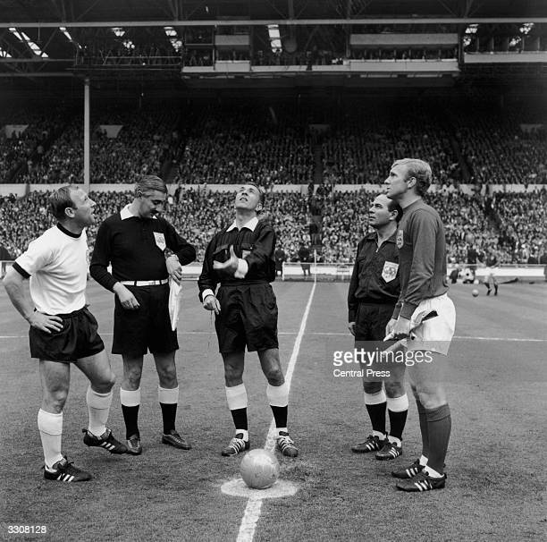 Referee Gottfried Dienst of Switzerland tosses the coin before the start of the World Cup final at Wembley between England and West Germany He is...