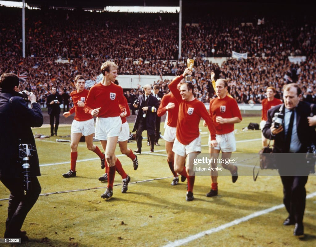 The England team raise the Jules Rimet trophy in the air following their 4-2 victory after extra time over West Germany in the World Cup Final at Wembley Stadium.
