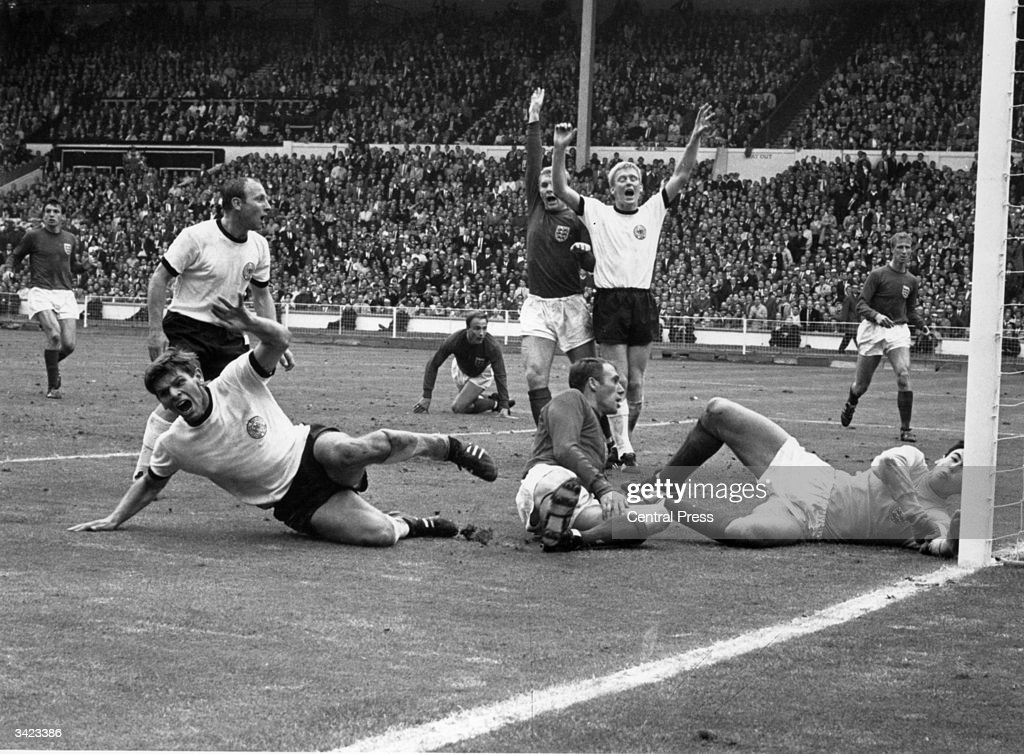 West Germany's Wolfgang Weber (on ground left) starts to celebrate after scoring past England's goalkeeper Gordon Banks, for an equaliser in the last minute of normal time in the World Cup Final at Wembley. England went on to win the 1966 World Cup 4-2 after extra time. Behind Weber is Uwe Seeler, with England's Ray Wilson on the ground next to Weber, Bobby Moore (1941 - 1993) and Schnellinger with arms raised, Jack Charlton (right) and George Cohen crawling to his feet.