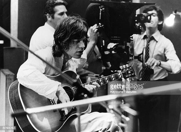 Mick Jagger singer of British rock band the Rolling Stones plays an acoustic guitar in a recording studio during the shooting of French director...