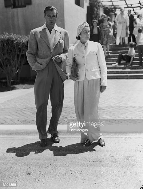 EXCLUSIVE Fulllength image of American actor Gary Cooper smoking a cigarette standing with his wife actor Sandra Shaw on a road in Southampton New...