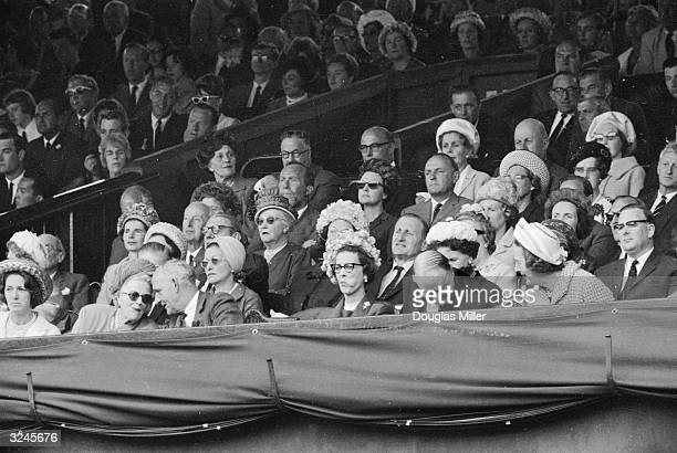 Princess Marina of Kent sucks on a sweet as she watches the play on Centre Court at Wimbledon