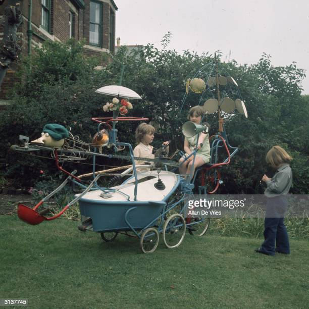 Children play with a tricycle constructed from discarded bric-a-brac and household goods.