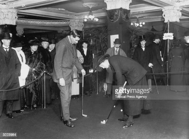 British golf champions James Braid and Charlotte 'Cecil' Leitch demonstrate the proper use of a golf club to customers at Harrods department store in...