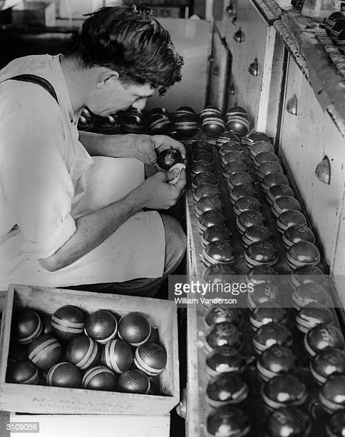 Cricket balls being polished by hand at A Reader's factory near Maidstone Kent before being packed.