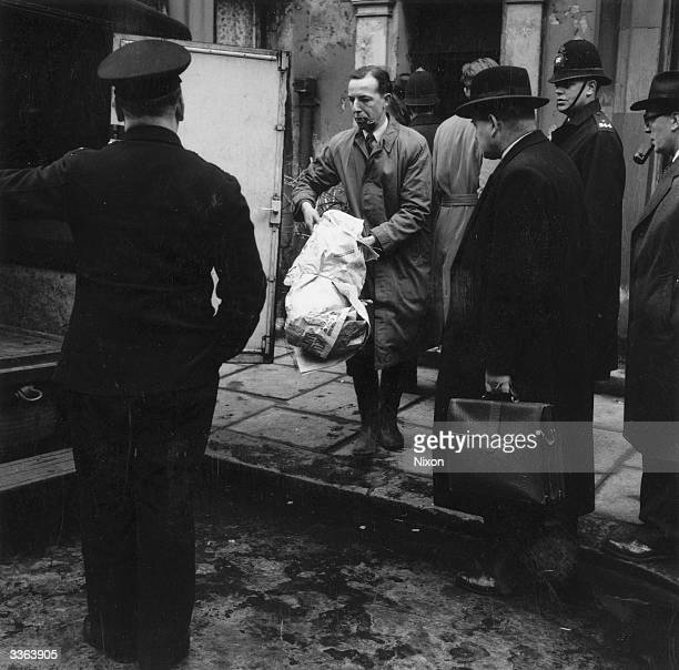 The bones of John Christie's fifth victim are removed from 10 Rillington Place London to a police van