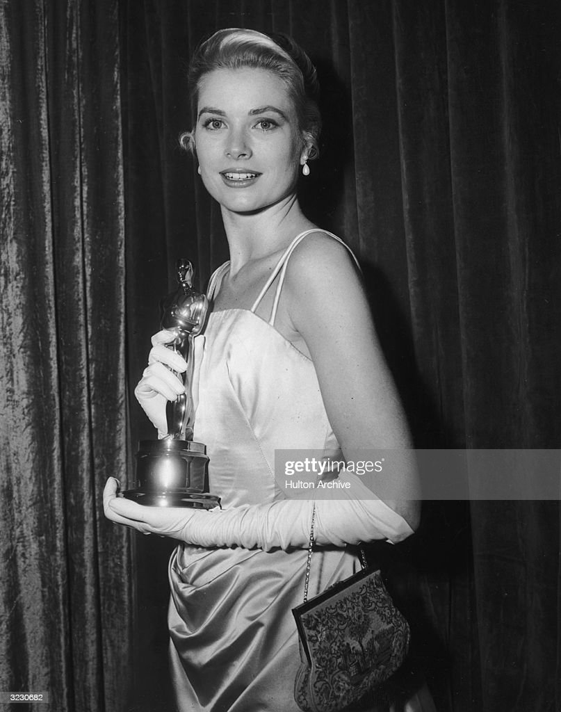 American actor Grace Kelly (1929 - 1982) poses in front of a curtain with her Best Actress Oscar for director George Seaton's film, 'The Country Girl,' at the Academy Awards, Los Angeles, California. She wears an evening gown with long white gloves.