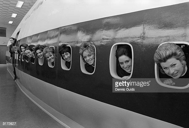 BOAC stewardesses peering through the port holes of the mockup Jumbo Jet 747 at London's Heathrow Airport during training for the introduction of...
