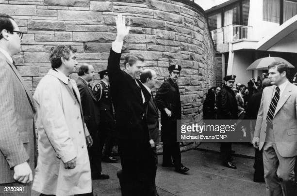 Surrounded by police officers and FBI agents, American statesman Ronald Reagan, the 40th President of the United States of America, waves to...