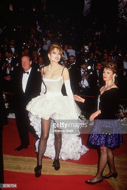 American actor Geena Davis walks up the red carpet wearing a white ruffled gown at the Academy Awards Los Angeles California An unidentified woman...