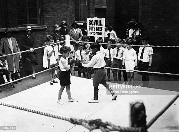 Small boys practise boxing for entertainment at a children's garden party