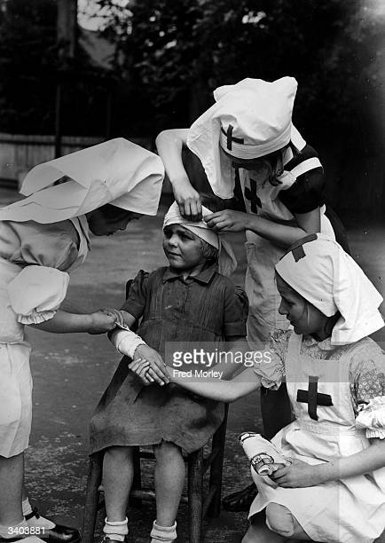 Pupils at the Church of England Infants School in Beddington, Surrey, practising first aid on each other. Left to right: Ann Moon, Janet North, Julia...