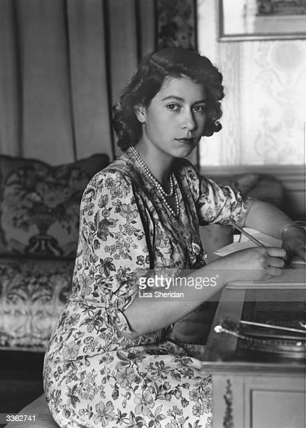 Queen Elizabeth II writing at her desk in Windsor Castle, Berkshire.