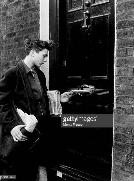 A delivery boy posting a newspaper through a letterbox