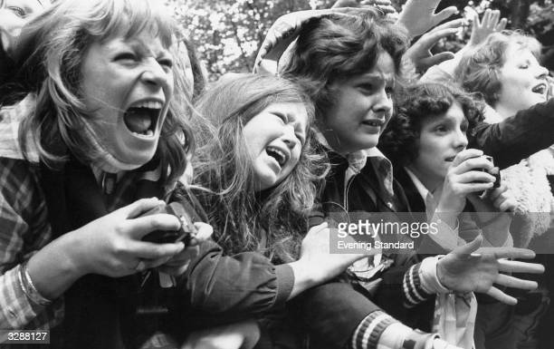 A crowd of overexcited teenage girls scream and cry at the sight of their idols pop group The Osmonds