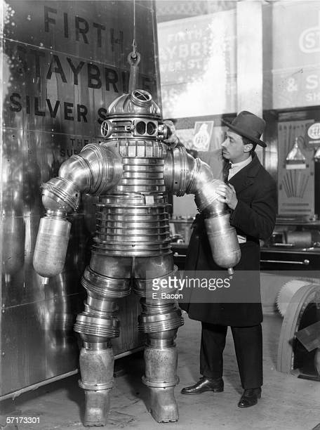 Inventor Joseph Salim Peress explains the workings of his new rustless diving suit made of Staybrite Silver Steel at the Olympia Shipping Exhibition...
