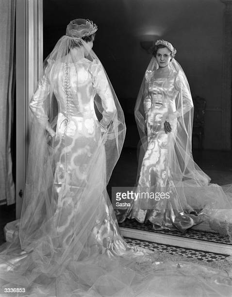 Actress Ann Todd models her wedding gown Designed and made by Helene Galin it is of white and silver damask satin with a cloud pattern and laced up...