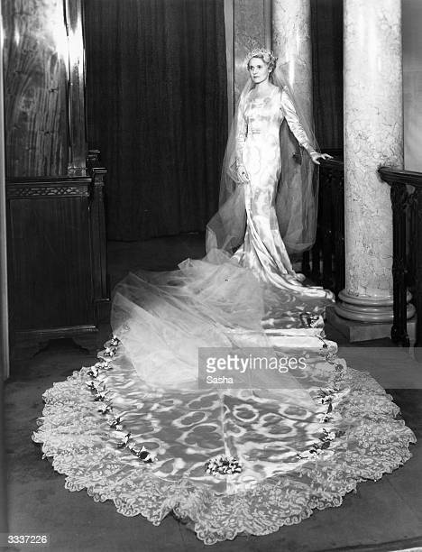 Actress Ann Todd models her wedding gown Designed and made by Helene Galin it is of white and silver damask satin with a cloud pattern A long train...
