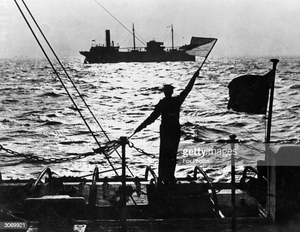 A sailor signals a merchant ship as it slowly passes the Naval Control Base in the Thames Estuary Inward bound convoys halt to take aboard pilots to...