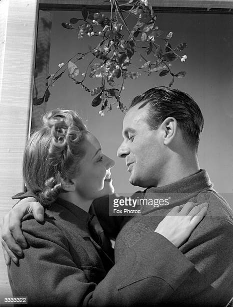 An Auxiliary Fire Servicewoman and a British Army private kissing under the mistletoe