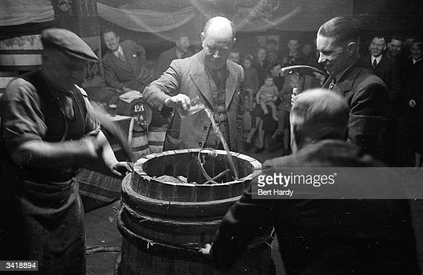 JG Daniell head brewer of the Ram Brewery Wandsworth pours a glass of beer over Ronnie Fordham who sits inside a barrel in the rough trussing...