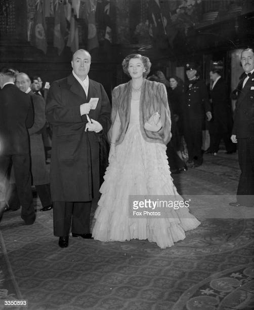 American film actress Myrna Loy and her husband arriving outside the Empire Theatre London for the Royal Command Film Performance of 'Scott of the...