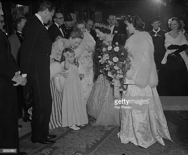 Auriol the five year old daughter of actress Phyllis Calvert meeting Queen Elizabeth Queen Consort to King George VI outside the Empire Theatre...