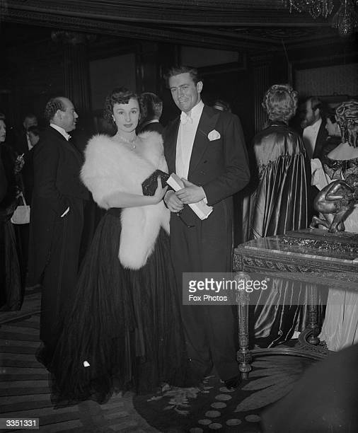 English film actress Googie Withers and her husband John McCullum in the foyer of the Empire Theatre, London, at the Royal Command Film Performance...