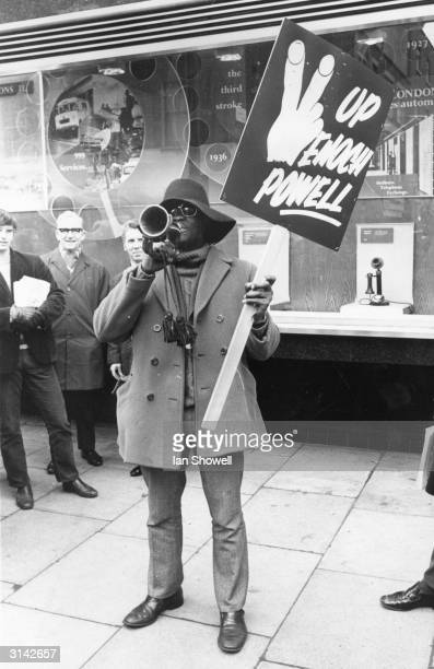 At the foot of the Post Office Tower a black postal engineer makes clear his views on antiimmigration MP Enoch Powell His placard reads 'Up Enoch...
