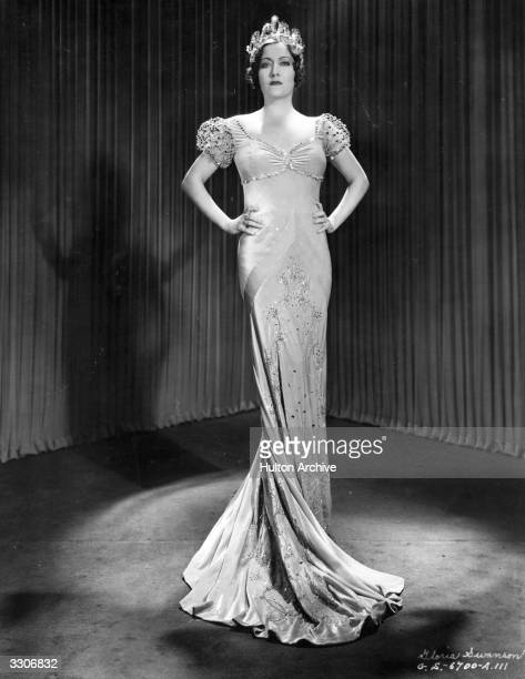 Actress Gloria Swanson wearing an orchid chiffon velvet 'Tosca' gown with diamonds, tiny mirrors and steel beads, designed by Chanel and worn with a...