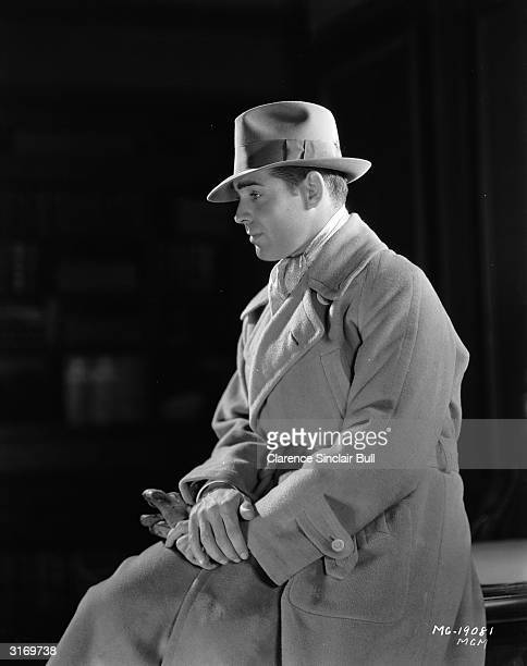 American actor Clark Gable in overcoat and trilby.