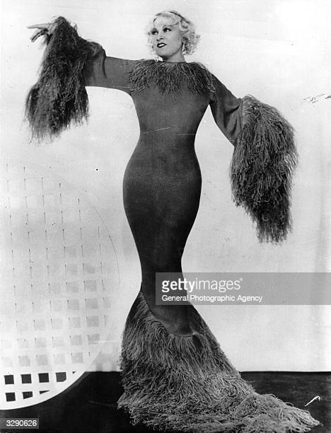 US vaudeville and film actress Mae West modelling an 'hourglass' evening dress