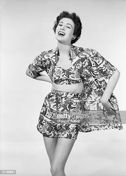 A woman modelling a summer outfit in a garishly patterned fabric comprising shorts a bikini top and a matching shirt
