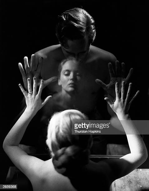 A couple pressing their hands against a pane of glass which is separating them representing the failure to communicate which can cause a marriage to...